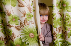 The little girl has hidden. The little girl looks out because of curtains Stock Image