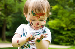 Little girl has painted herself painting. Outdoors Stock Images