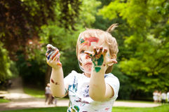 Little girl has painted herself painting. Outdoors Royalty Free Stock Images