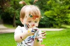 Little girl has painted herself painting. Outdoors Royalty Free Stock Photography