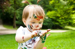 Little girl has painted herself painting. Outdoors Stock Photography
