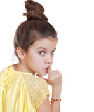 Little girl has put forefinger to lips as sign of silence Stock Image