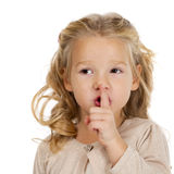 Little girl has put forefinger to lips as sign of silence Royalty Free Stock Images