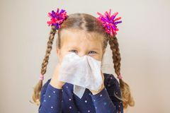 The little girl has a runny nose and blows her nose into a paper royalty free stock images