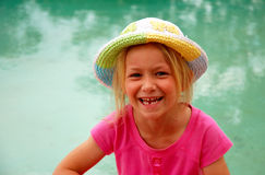 Little girl with hat. Outdoor portrait of a cute little Caucasian blond girl wearing a colorful hat with happy smiling facial expression showing her lost tooth stock photography