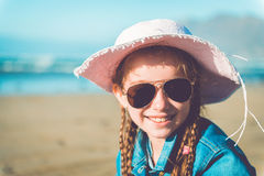 Little girl in a hat on the  beach Stock Photos