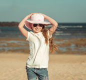 Little girl in a hat on the  beach Stock Image