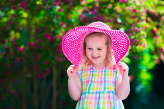 Little girl in a hat in blooming summer garden Royalty Free Stock Image