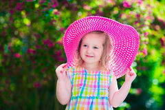 Little girl in a hat in blooming summer garden Stock Photo