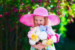 Little girl in a hat in blooming summer garden Stock Photography