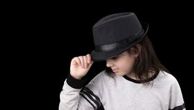 Little girl in a hat with a brim on a black background.  stock photos