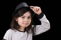 Little girl in a hat with a brim on a black background.  royalty free stock photo