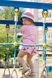 Little girl in hat climbs on children playground at sunny d Stock Photo