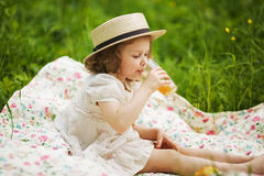 Little girl in a hat drinking a juice Royalty Free Stock Photo