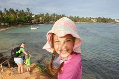 Little girl with a hat on a family hike by the tropical sea. Travelling with children, beach hopping, family time, active lifestyle, beach fun concept royalty free stock photography
