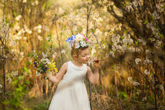 The little girl in a hat from flowers in the wood Stock Photos