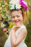 The little girl in a hat from flowers in the wood Stock Image