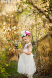 The little girl in a hat from flowers in the wood Royalty Free Stock Image