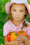Little girl in hat holding pepper Stock Photo