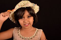 Little girl with a hat looking at camera against a black backdrop royalty free stock image
