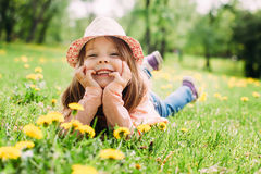 Little girl with hat lying on the grass Stock Photos
