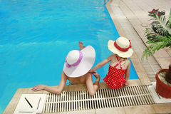 Little girl in a hat with mother in swimming pool Stock Photography