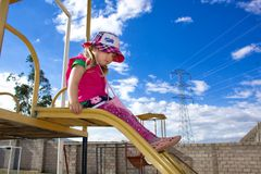 A little girl in a hat of Panama, rolls down the hill on a children`s playgrond. Behind her beautiful scenery and mountains. Summe stock image