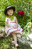 Little girl in a hat on a picnic. On the green background with a red flower Stock Photography
