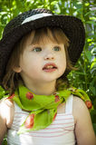 Little girl in a hat on a picnic. On the green background with a red flower Royalty Free Stock Photo