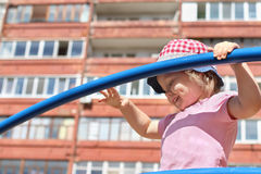 Little girl in hat plays on children playground at sunny da Royalty Free Stock Images