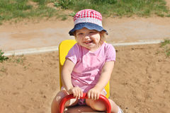 Little girl in hat plays on seesaw on children playground Stock Photography