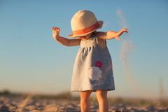 A little girl in a hat pours sand on the beach stock images