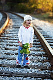Little girl in hat on railroad tracks Stock Photo