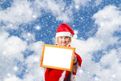 Little girl in hat of Santa Claus on background of sky Stock Image