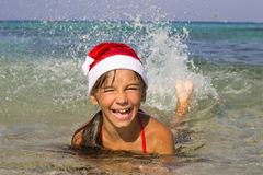 Little girl in the hat of Santa Claus swims Royalty Free Stock Photography