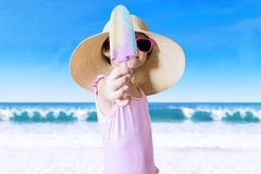 Little girl with hat showing ice cream Royalty Free Stock Photo