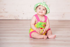 The little girl in the hat sitting on the floor stock image