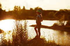 Little girl in hat stands on the river bank at sunset Stock Images