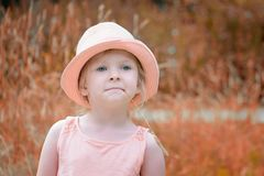 A little girl in a hat with a straw in her mouth. A beautiful child with blond hair. Stock Photo
