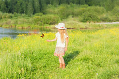 Little girl in a hat on a summer day playing with a butterfly in a field in the village Royalty Free Stock Photography