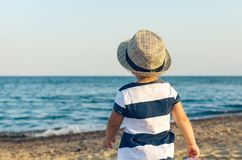 Little girl in a hat walks along the seashore royalty free stock photography