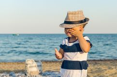 Little girl in a hat walks along the seashore stock images