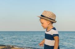 Little girl in a hat walks along the seashore stock photo