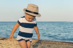 Little girl in a hat walks along the seashore stock image