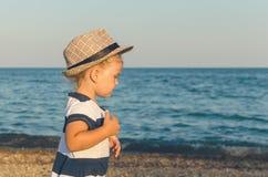 Little girl in a hat walks along the seashore stock photos