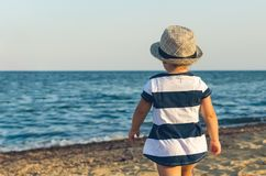 Little girl in a hat walks along the seashore stock photography