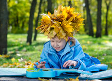 Little girl with a hat of yellow autumn leaves Stock Photography