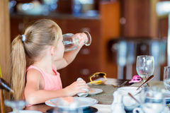 Little girl have breakfast drinking water at outdoor cafe Royalty Free Stock Photo