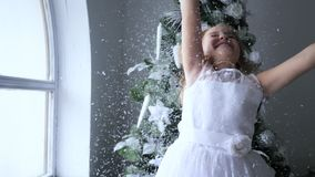 Little girl have fun with artificial snow on winter photoshoot beside christmas tree, atmosphere of new year stock video footage