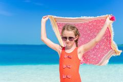 Little girl have fun with beach pareo on tropical vacation. Little girl have fun with beach towel during tropical vacation Royalty Free Stock Image